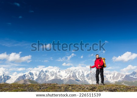 Hiker with backpack standing high in the mountain and enjoying the view  - stock photo