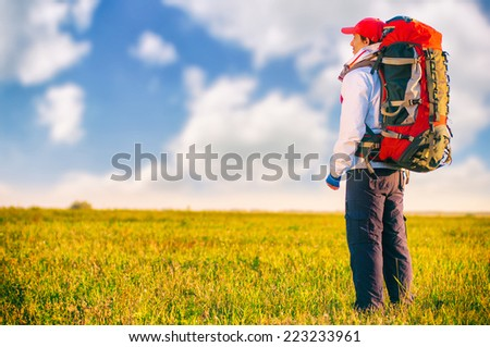 Hiker with backpack standing in the field. Summer healthy active lifestyle. Single travel. - stock photo