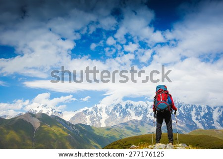 Hiker with backpack standing in the mountains and enjoying the view