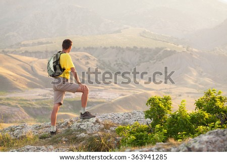Hiker with backpack standing on a rock  over valley