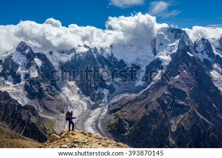 Hiker with backpack standing on mountain top and enjoying scene - stock photo