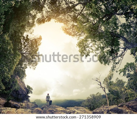 Hiker with backpack standing on the rock surrounded by lush tropical forest - stock photo