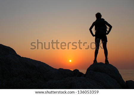 Hiker with backpack standing on top of a mountain and enjoying sunset - stock photo