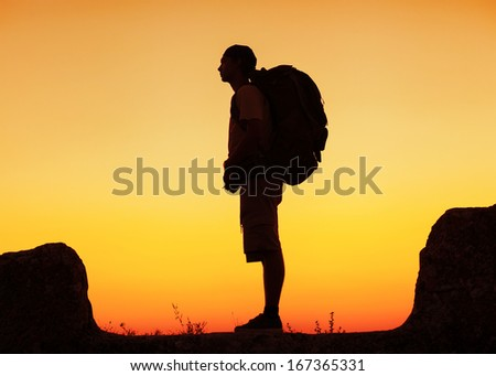 Hiker with backpack standing on top of a mountain and enjoying sunset