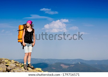 Hiker with backpack standing on top of a mountain and enjoying the view  - stock photo