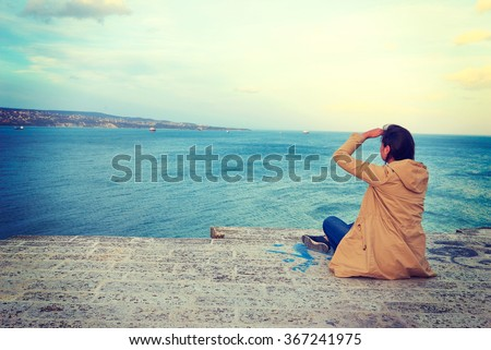 Hiker with backpack standing on top of a mountain and looks into the distance on blue sea in Bulgaria - stock photo