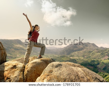 Hiker with backpack standing on top of a mountain with raised hands and enjoying landscape. - stock photo