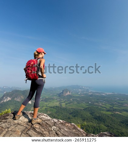 Hiker with backpack standing on top of the mountain - stock photo