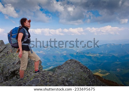 Hiker with backpack standing on top of the mountain and looks into the distance. Freedom concept. Autumn mountain travel.