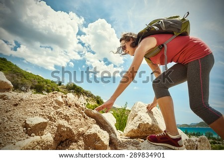 Hiker with backpack walking on a rocky terrain looking at beautiful landscape motivation and inspiration.