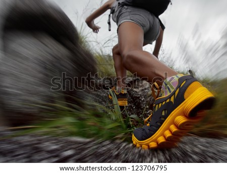 Hiker with backpack walking through rocky motion blurred terrain - stock photo