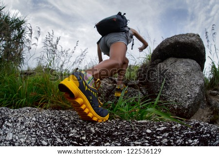 Hiker with backpack walking through rocky terrain - stock photo