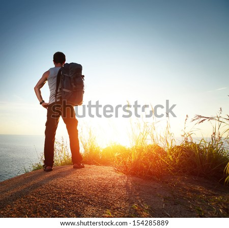 Hiker with backpack watching sunset over sea - stock photo