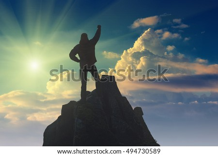 Hiker with raised hand standing on a cliffs edge against the sun. The top of the mountain. Colorful clouds in a light of sunrise.