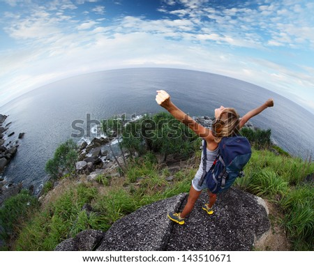 Hiker with raised hands standing on top of a mountain - stock photo