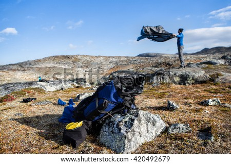 Hiker with sleeping bag in the morning on the campground - stock photo