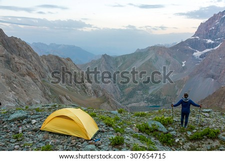 Hiker with walking poles and climbing tent. Man observing scenic evening view of mountain valley yellow camping tent on grassy rocky place - stock photo