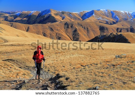 Hiker woman across the mountain trails, Romania - stock photo