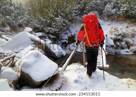 Hiker woman carrying a backpack across snow covered wooden bridge - stock photo