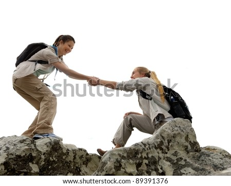 Hiker woman helps her friend climb up the last section of mountain. teamwork in outdoor lifestyle adventure - stock photo