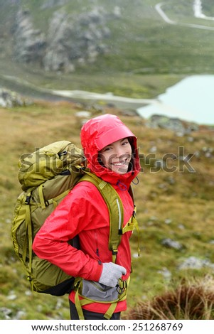 Hiker woman hiking with backpack in rain on trek living healthy active lifestyle. Smiling cheerful girl walking on hike in beautiful mountain nature landscape while raining in Swiss alps, Switzerland. - stock photo