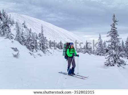 Hiker woman in a snowy forest and cliff