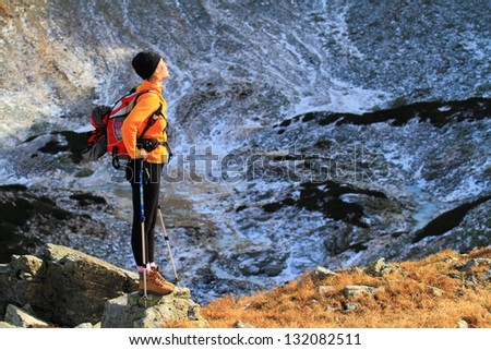 Hiker woman standing and admiring the beautiful mountains and valleys - stock photo
