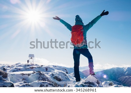 Hiker woman standing with hands up achieving the top, admiring winter mountain landscape. Happy tourist woman in winter. High Tatras, 1987 meter above sea level. Poland, Slovakia - stock photo