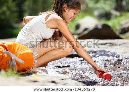 Hiker woman taking water in river in Yosemite National Park after hiking. Happy girl smiling enjoying outdoors summer trekking vacation. Multicultural woman in California, USA. - stock photo