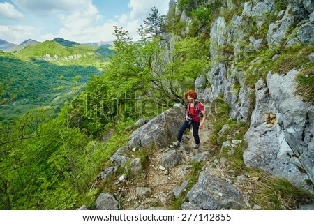 Hiker woman with backpack and camera on a trail in the mountains - stock photo