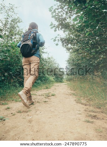 Hiker woman with backpack walking on path among trees in summer forest - stock photo