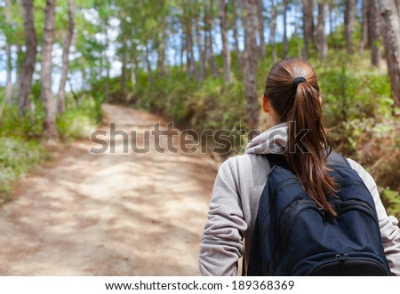 Hiker woman with backpack walking through a forest.  - stock photo