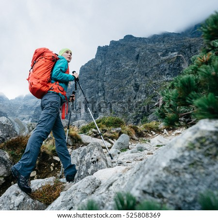 Hiker woman with backpack walking up the trail with beautiful mountain peaks view landscape.  Hiking in a stormy weather, active lifestyle.