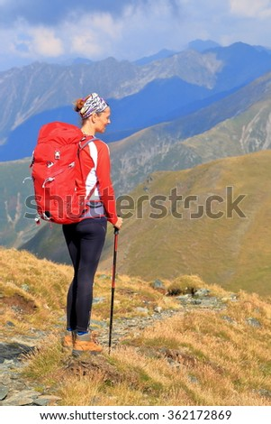 Hiker woman with red backpack standing on sunny mountain trail - stock photo