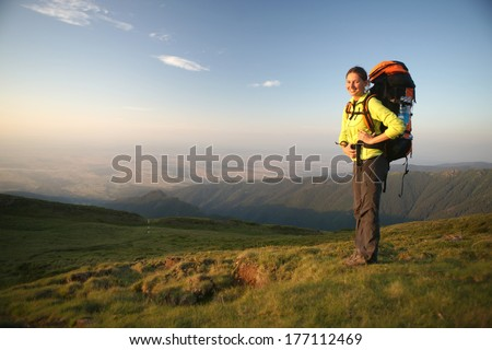 Hiker women standing in the mountains in the sunset. Free space of a plane behind her.