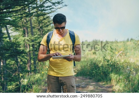 Hiker young man in sunglasses working on digital tablet PC in summer forest - stock photo