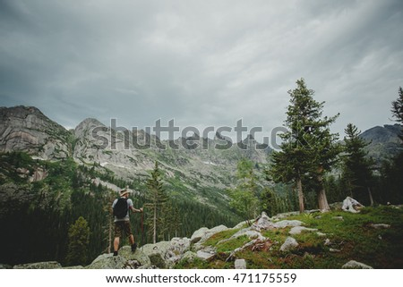 Hiker young man with backpack and trekking of cliff and looking at the mountains in summer outdoor