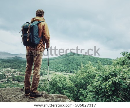 Hiker young man with backpack and trekking poles standing on edge of cliff and looking at the mountains