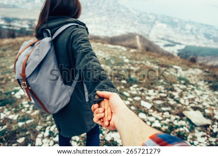 Hiker young woman holding man's hand and leading him on nature outdoor. Couple in love. Focus on hands. Image with instagram filter - stock photo