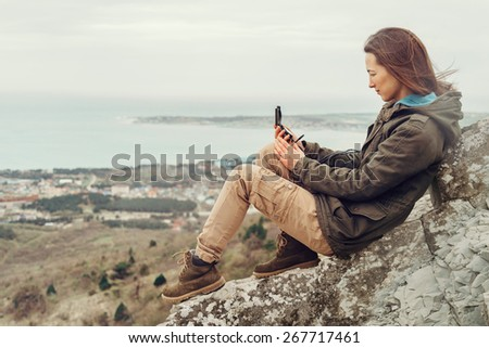 Hiker young woman sitting on stone and searching direction with a compass outdoor