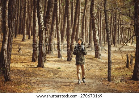 Hiker young woman walking in a pine forest - stock photo
