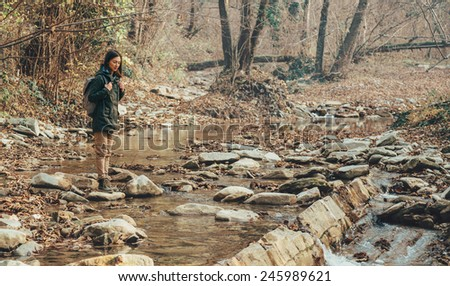 Hiker young woman with backpack crossing a river on stones in autumn forest. Hiking and travel theme - stock photo