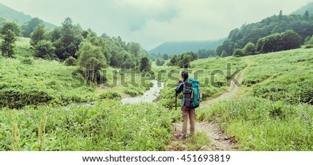 Hiker young woman with backpack photographing the nature in summer valley