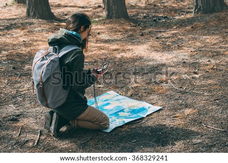Hiker young woman with backpack searching direction with a compass and map in the forest - stock photo
