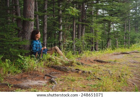 Hiker young woman with backpack sitting near the tree in summer forest - stock photo