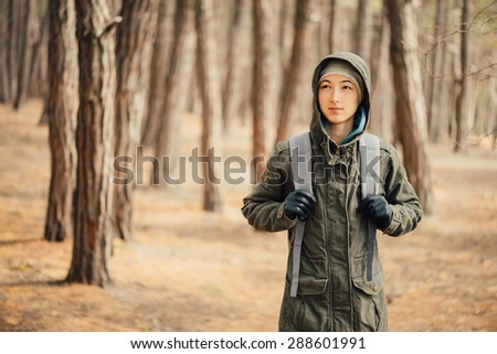 Hiker young woman with backpack walking in the pine forest - stock photo