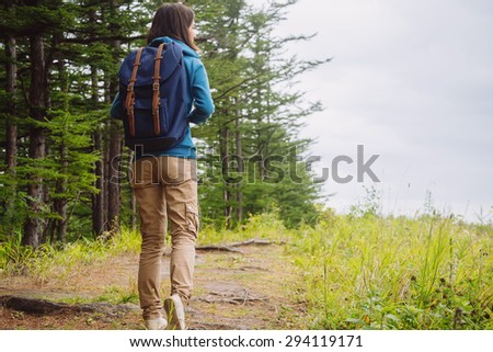 Hiker young woman with backpack walking on path in summer forest, rear view. Space for text in right part of image - stock photo