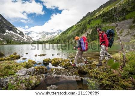Hikers are walking by mountain lake in Altai mountains, Russia - stock photo