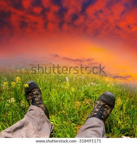 hikers feet in a grass on a sunset background - stock photo