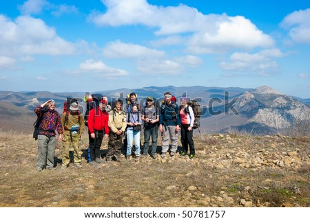 Hikers group on a peak in mountains - stock photo